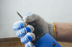 Closeup of male hand with blue screwdriver against white wall and floor stock image