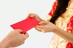 Red money envelop for Chinese new year. Closeup male hand giving blank red envelopes with money while young woman with Traditional Chinese costume dress Royalty Free Stock Photography