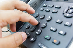 Closeup of male hand holding telephone receiver while dialing a telephone number to make a call stock photos