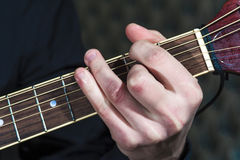 Closeup of male hand playing on acoustic guitar Royalty Free Stock Photo
