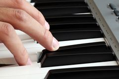 Closeup of a male hand playing a piano Royalty Free Stock Photos