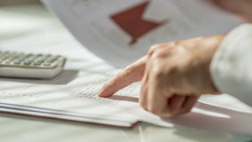 Closeup of male hand pointing to figures written on a document. Or report in form of statistical data. Conceptual of economy, finance and accounting stock photography
