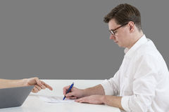 Closeup of male hand pointing where to sign a contract, legal papers or application form. Royalty Free Stock Image