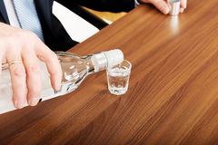 Closeup on male hand pouring vodka into a glass Stock Photo