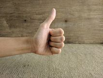 Closeup of male hand showing thumbs up sign stock image