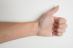 Closeup of male hand showing thumbs up on white background Stock Images