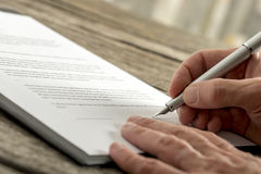 Closeup of male hand signing a contract or application form. With fountain pen on textured wooden desk Royalty Free Stock Image