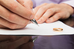 Closeup of male hand signing divorce papers Stock Photos