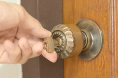 Closeup of male hand unlocking old door. Knob Royalty Free Stock Photo