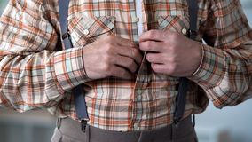 Closeup of male hands buttoning up checkered shirt, old-fashioned clothes. Stock photo royalty free stock photography