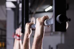 Closeup of male hands holding a pull ups bar. Closeup detail of male hands holding a pull-ups bar in a gym stock photos