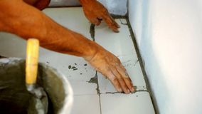 Closeup male hands laying ceramic floor tiles stock video footage