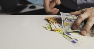 Closeup of male hands taking a lot of money from the table. Denominations: two hundred euros, one hundred euros, fifty euros, one hundred dollars stock video