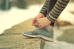 Closeup of male hands tying shoelaces in winter. Closeup of male hands tying shoelaces outdoor in winter nature. Running, jogging, fitness workout Stock Photos