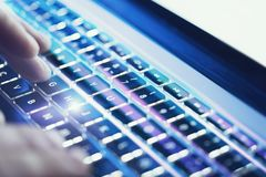 Closeup of male hands typing on laptop keyboard at the office. Visual effects, flares. stock photography