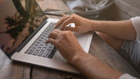 Closeup of male hands typing on laptop in tropical cafe stock footage