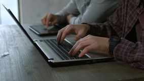 Hands typing text on laptop keyboard and tablet. Closeup male hands typing on modern laptop keyboard and browsing the net on digital tablet pc on the wooden stock video