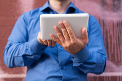 Closeup of male hands using a white digital tablet. Wall behind him Stock Image
