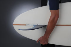 Closeup Male Holding Surf Board. Closeup of a teenage male wearing a wet suit holding a surf board. Horizontal format over a light to dark gray background Stock Photography