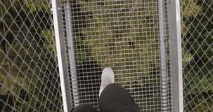 Closeup of male legs walking on a metal suspension bridge in the mountains. stock video footage