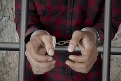 Male prisoner with handcuffs in the jail. Closeup of a male prisoner hands with handcuffs while standing behind bars. Shot in the jail Royalty Free Stock Photo