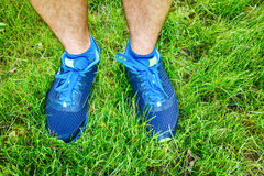 Closeup of a male runner standing in grass. Closeup of a male runner standing - space for text. Fitness concept Royalty Free Stock Image