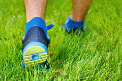 Closeup of a male runner standing in grass. Closeup of a male runner standing - space for text. Fitness concept Royalty Free Stock Images