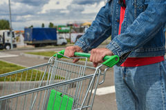 Male shopper with trolley. Closeup of male shopper with trolley at parking of supermarket Royalty Free Stock Photo