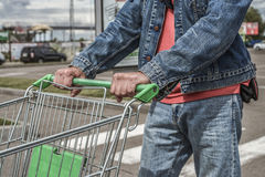 Male shopper with trolley. Closeup of male shopper with trolley at parking of supermarket Stock Photo