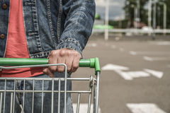 Male shopper with trolley. Closeup of male shopper with trolley at parking of supermarket Royalty Free Stock Image