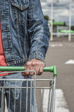 Male shopper with trolley. Closeup of male shopper with trolley at parking of supermarket Royalty Free Stock Images