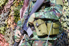 Closeup male soldier hands holding machine gun, selective focus. On hand Stock Images