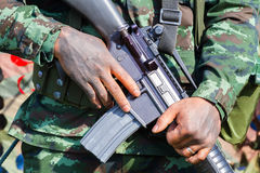 Closeup male soldier hands holding machine gun, selective focus. On hand Stock Photo