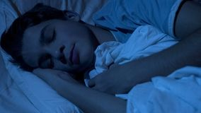 Closeup of male teenager face sleeping deeply at night time, feeling relaxed. Stock photo royalty free stock image
