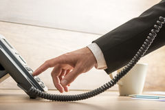 Closeup of male telemarketing operator dialing a telephone numbe Stock Photos