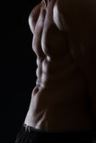Closeup on male torso with abdominal muscles. Closeup on muscular male torso with abdominal muscles on black Royalty Free Stock Image