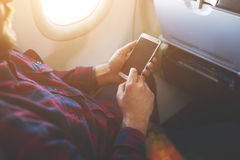 Closeup of male is watching photos on mobile phone while flying in an airplane Royalty Free Stock Photography