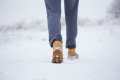 Closeup of male yellow winter shoes on snow.  Stock Photo