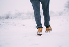 Closeup of male yellow winter shoes on snow Stock Photos