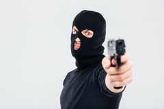 Closeup of man in balaclava standing and aiming with gun Royalty Free Stock Photos