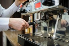 Closeup of a man barista brewing an espresso using a coffee mach. Ine in a coffee shop Royalty Free Stock Image