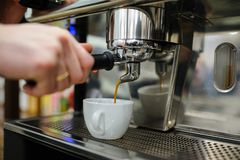 Closeup of a man barista brewing an espresso using a coffee mach. Ine in a coffee shop Royalty Free Stock Images