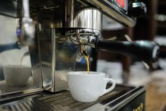 Closeup of a man barista brewing an espresso using a coffee mach. Ine in a coffee shop Stock Photography