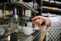 Closeup of a man barista brewing an espresso using a coffee mach. Ine in a coffee shop Stock Image