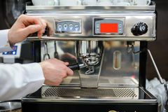 Closeup of a man barista brewing an espresso using a coffee mach. Ine in a coffee shop Royalty Free Stock Photo