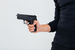 Closeup of man in black clothes holding a gun Stock Images