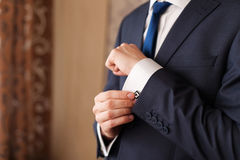 Closeup of a man in black suit correcting a sleeve.  Royalty Free Stock Photo