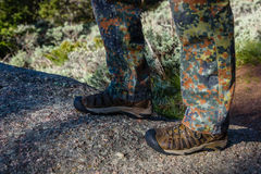 Closeup of man boots and camouflage pants, trousers while hiking on trail in the mountains. Man`s hiking shoes and legs closeup o Stock Images