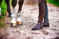 Closeup of man in boots and his horse. Outdoors Royalty Free Stock Photography