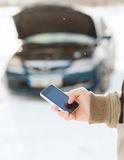 Closeup of man with broken car and cell tphone. Transportation, winter and vehicle concept - closeup of man with broken car and cell phone Stock Image